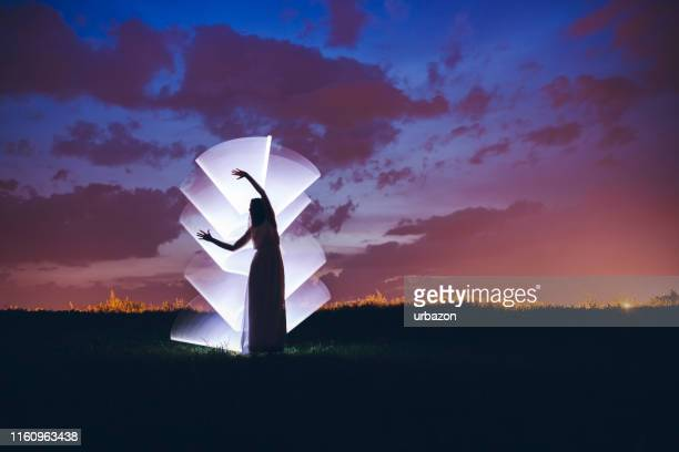 woman in nature in front of light painting - spiritual enlightenment stock pictures, royalty-free photos & images