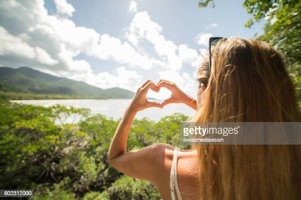Woman in nature makes heart shape finger frame