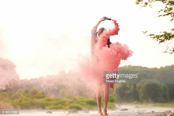 Woman in nature with red smoke around her