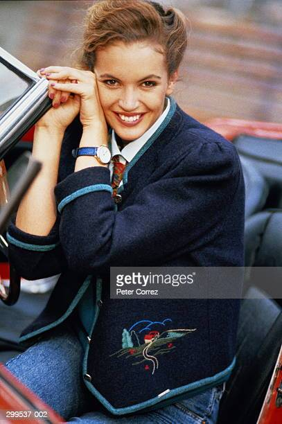 Woman in navy blazer sitting in red sports car