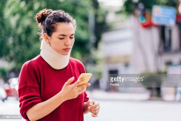 woman in neck brace using mobile phone on street - injured stock pictures, royalty-free photos & images