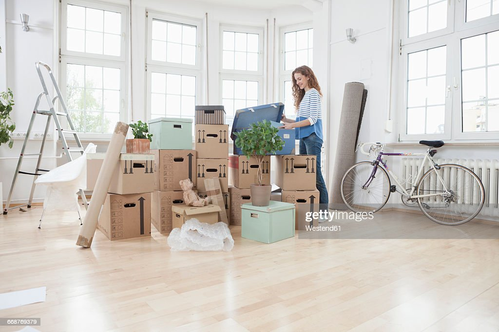 Woman in new apartment unpacking cardboard box : Stock Photo