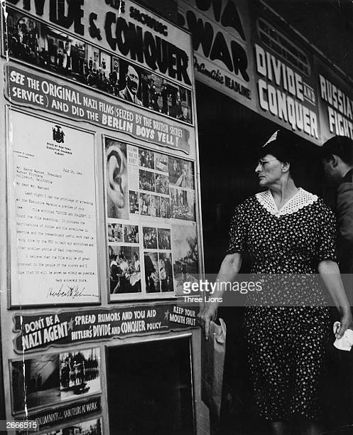 A woman in new York examining a poster for a series of captured Nazi films to be shown in America