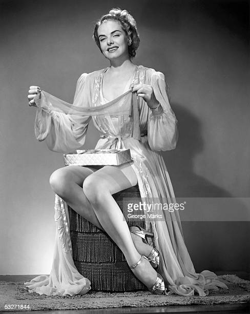 woman in night gown holding stockings - vintage garter belt stock photos and pictures