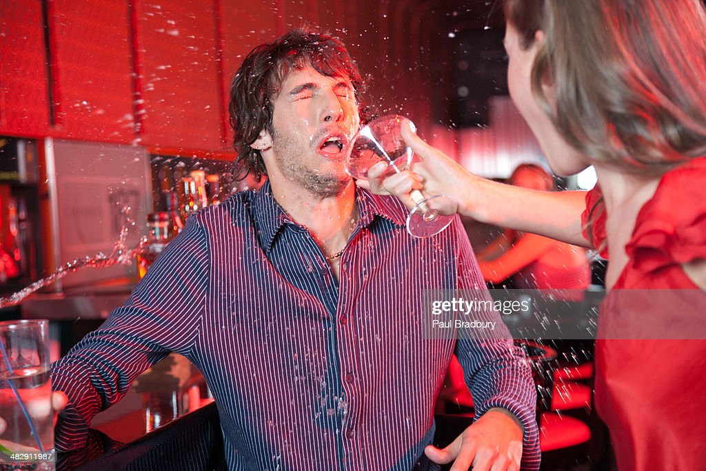 Woman in nightclub throwing beverage in man's face : Stock Photo