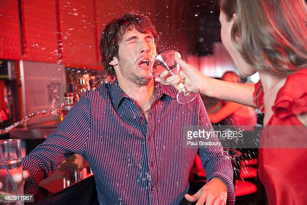 woman in nightclub throwing beverage in man's face - couple arguing stock photos and pictures