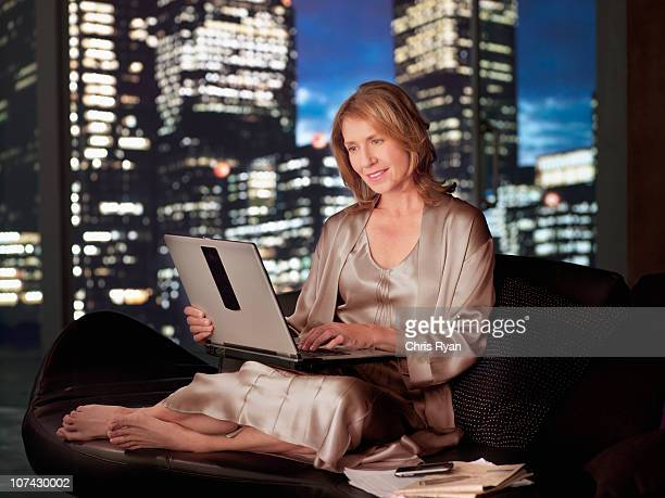 woman in nightgown using laptop at night - women in slips stock photos and pictures
