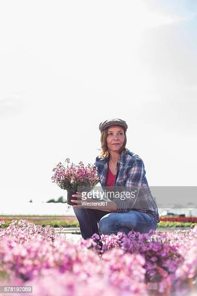 Woman in nursery holding flower