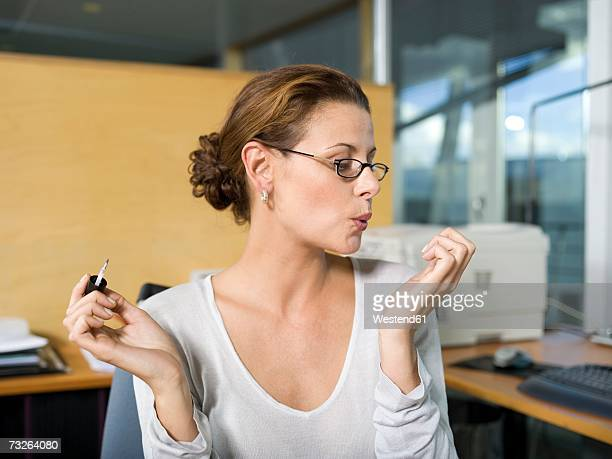 Woman in office, applying nail polish, blowing, close-up
