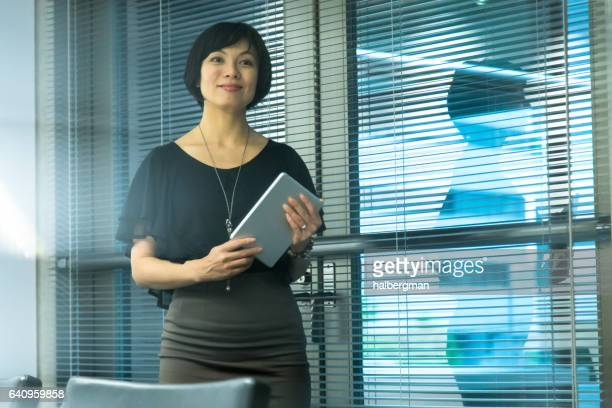Woman in Office Holding Digital Tablet