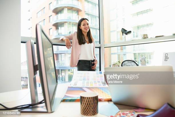 woman in office looking at camera - femalefocuscollection stock pictures, royalty-free photos & images