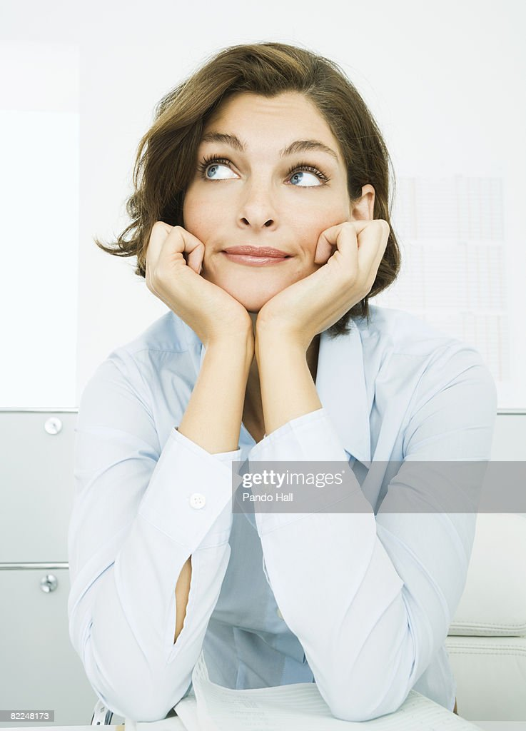 Woman in office, looking up : Stock Photo