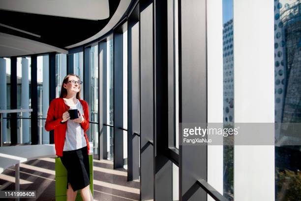 woman in office smiling in sunshine in window drinking coffee - day 1 stock pictures, royalty-free photos & images