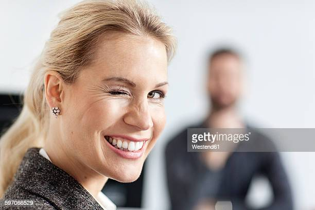 Woman in office twinkling with man in background