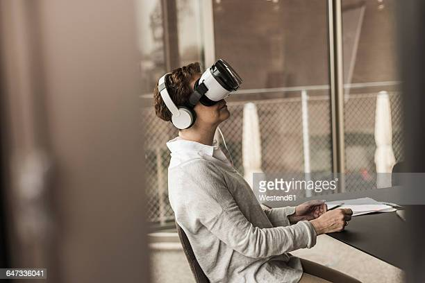 Woman in office wearing virtual reality glasses