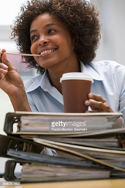 Woman in office with cup of coffee on pile of files