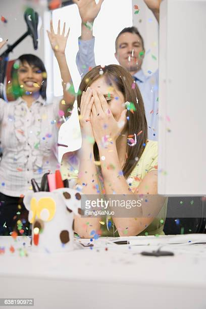 Woman in office with hands on face during celebration surprise