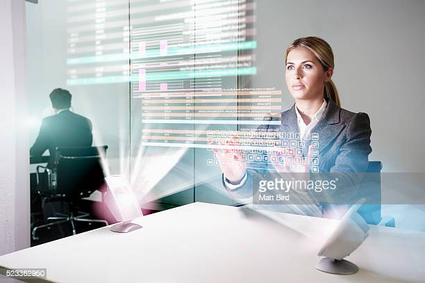 Woman in office working on futuristic device