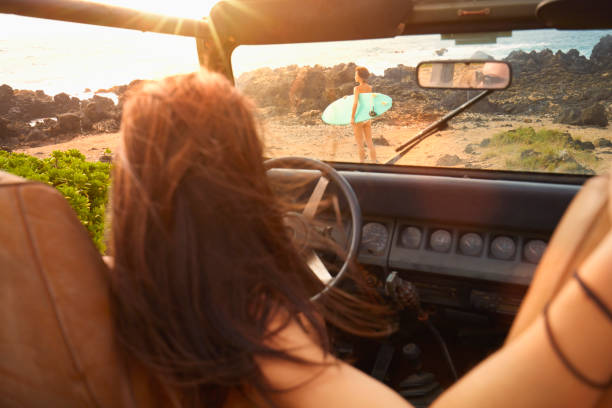 Woman in off-road vehicle watching friend carrying surfboard