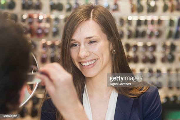 woman in opticians assisting customer, smiling - sigrid gombert stock pictures, royalty-free photos & images