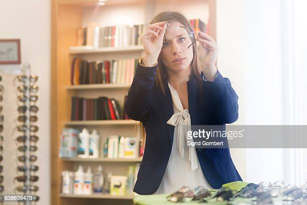 woman in opticians looking at pair of glasses - sigrid gombert stock pictures, royalty-free photos & images