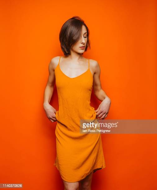 woman in orange dress on orange background - orange farbe stock-fotos und bilder