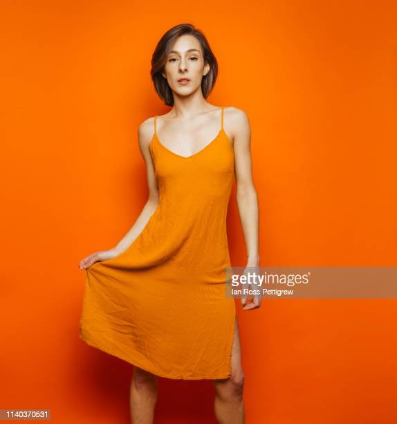 woman in orange dress on orange background - orange dress stock pictures, royalty-free photos & images