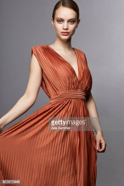 woman in orange dress - kleid stock-fotos und bilder