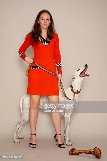 Woman in orange dress with greyhound on leash, portrait