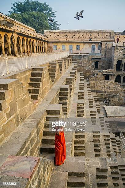 woman in orange sari carrying container in chand baori - abhaneri stock photos and pictures