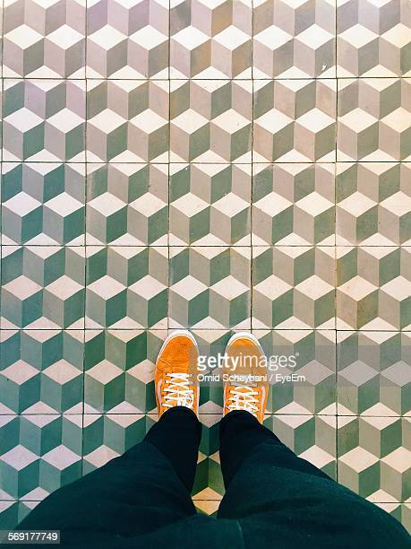 Woman in orange shoes standing on tiled floor
