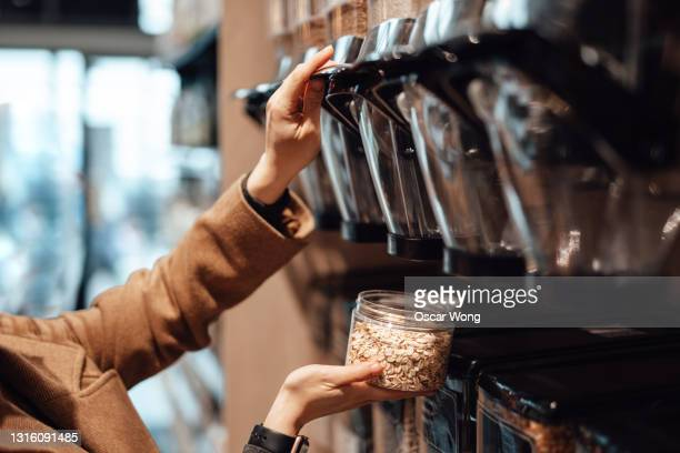 woman in organic whole foods refilling store dispensing oats into a reusable container. - sustainable lifestyle stock pictures, royalty-free photos & images