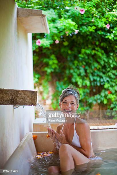 woman in outdoor bath at spa in mexico - one mature woman only stock pictures, royalty-free photos & images