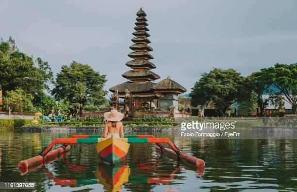 woman in outrigger at pura ulu danau temple against sky - lake bratan area stock pictures, royalty-free photos & images