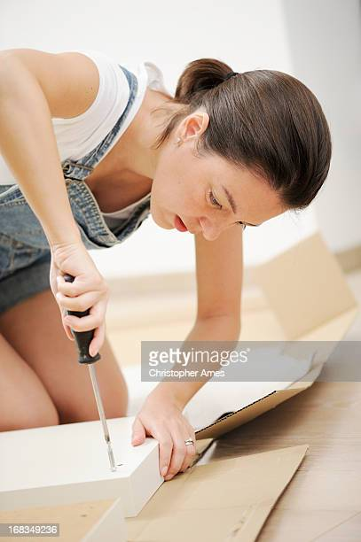 Woman in overalls assembling flat pack furniture