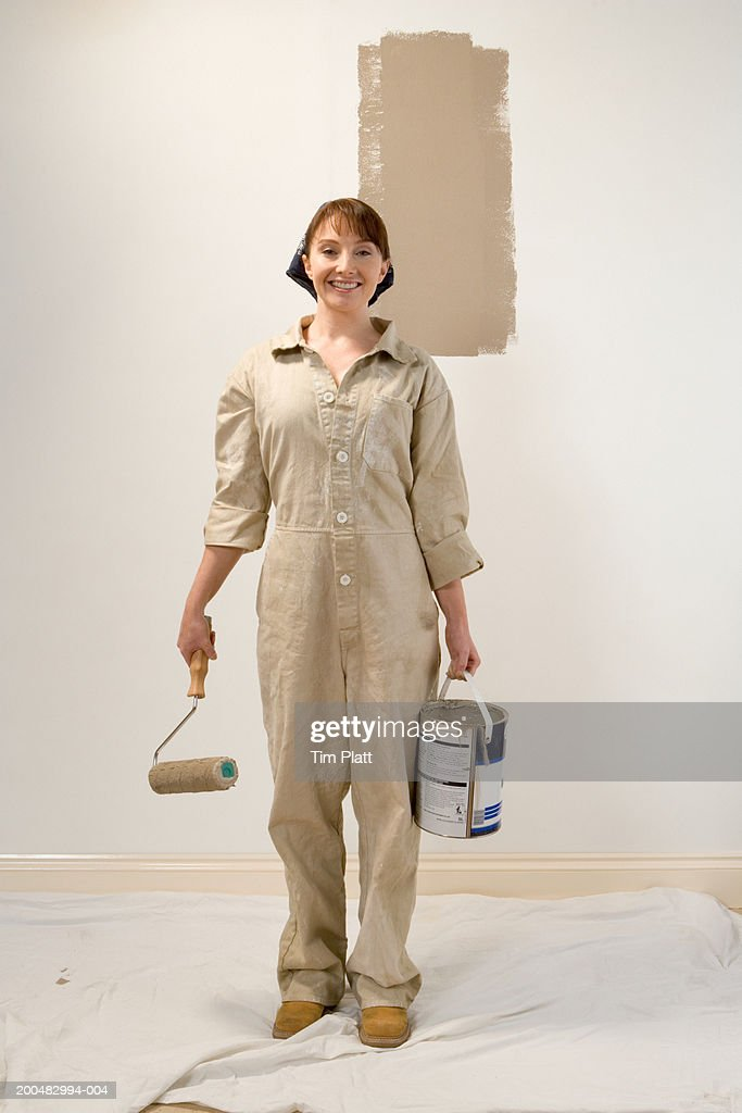Woman in overalls holding paint can and roller, portrait : Stock Photo