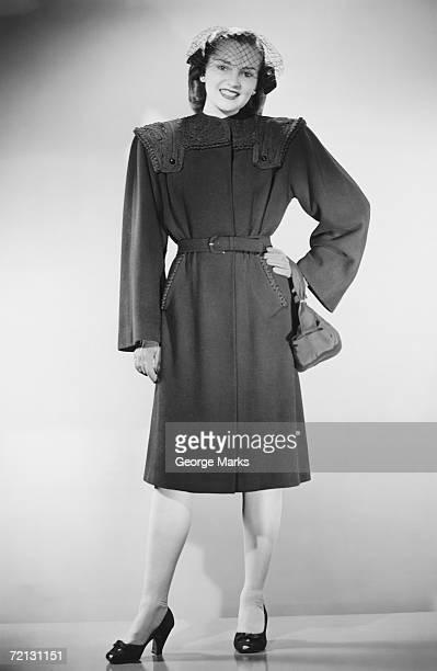 Woman in overcoat posing in studio (B&W), portrait