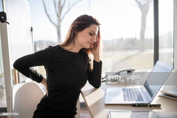 woman in pain working in the office - backache stock pictures, royalty-free photos & images