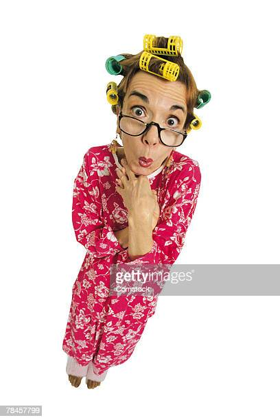 Woman in pajamas and curlers with embarrassed expression
