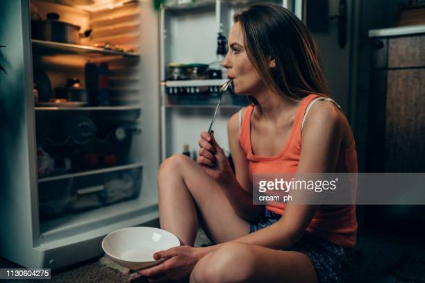 woman in pajamas in front of the refrigerator late night - eating disorder stock pictures, royalty-free photos & images