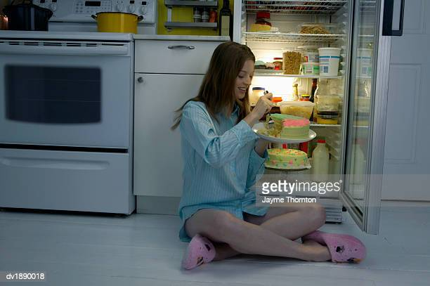 Woman in Pajamas Sits on Kitchen Floor Next to a Fridge Eating a Cake