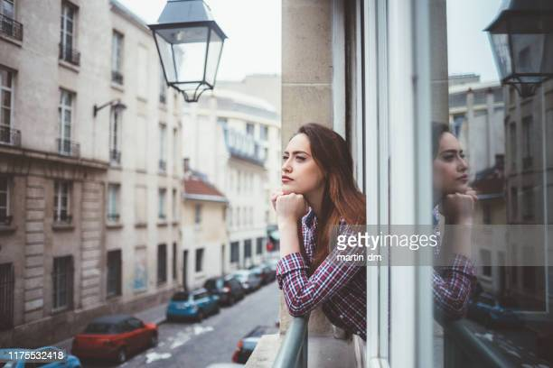 woman in paris looking through the window - stereotypical homemaker stock pictures, royalty-free photos & images