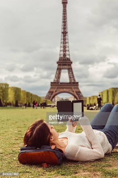 Woman in Paris reading e-book