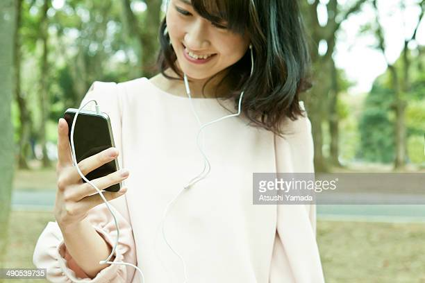 Woman in park listening to music on smartphone
