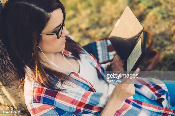 woman in park reading an e-book - e reader stock pictures, royalty-free photos & images