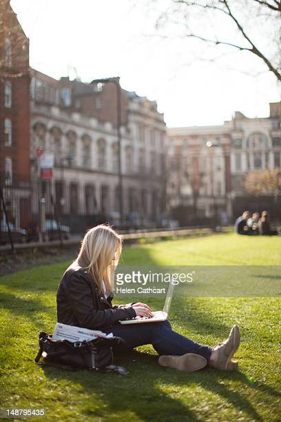 Woman in park working on laptop