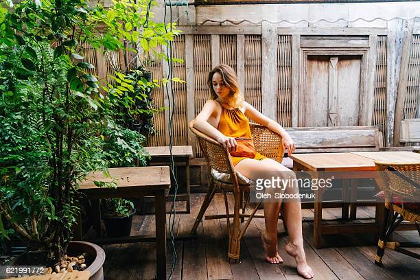 woman in patio - orange dress stock pictures, royalty-free photos & images