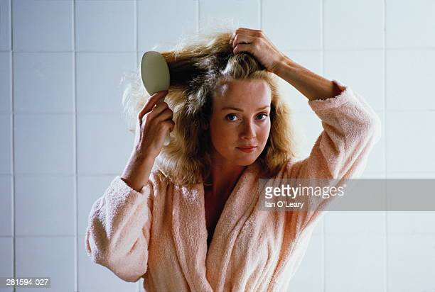 Woman in peach dressing gown brushing hair,white tiles behind