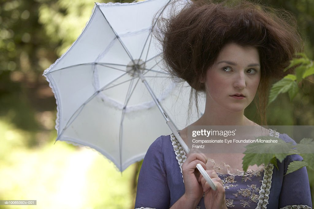 Woman in period dress holding parasol : Foto stock