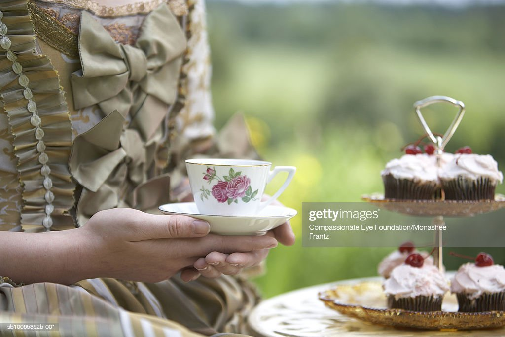 Woman in period dress holding tea cup, mid section : Foto stock